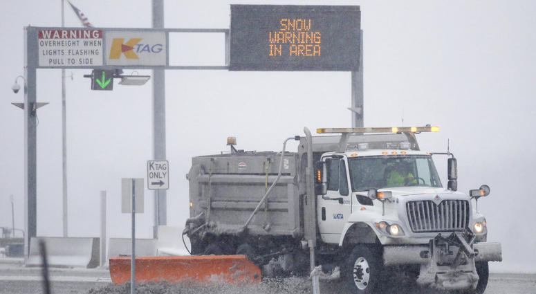 A plow removes snow at an entrance of the Kansas Turnpike near Lawrence, Kan., Sunday, Nov. 25, 2018.