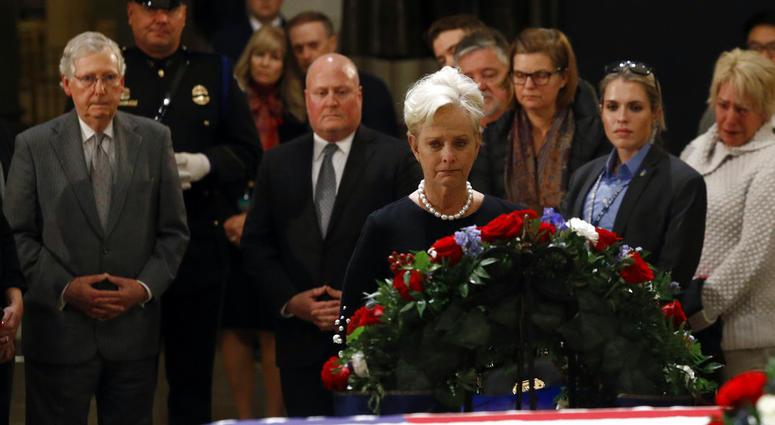 Cindy McCain, center, widow of the late U.S> Sen. John McCain, R-Ariz., views the flag-draped casket of former President George H.W. Bush as he lies in state in the Capitol Rotunda in Washington, Tuesday, Dec. 4, 2018.