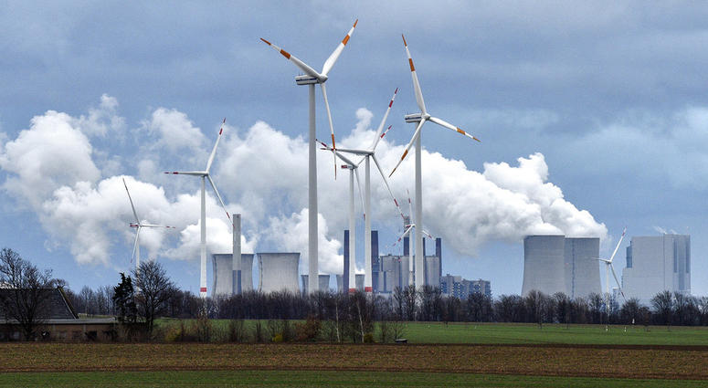 Renewable and fossil-fuel energy is produced when wind generators are seen in front of a coal fired power plant near Jackerath, Germany, Friday, Dec. 7, 2018.