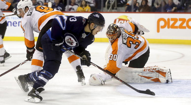 Winnipeg Jets' Brandon Tanev (13) scores against Philadelphia Flyers' goaltender Michal Neuvirth (30) after getting past Flyers' Ivan Provorov (9) during second-period NHL hockey game action in Winnipeg, Manitoba, Sunday, Dec. 9, 2018.