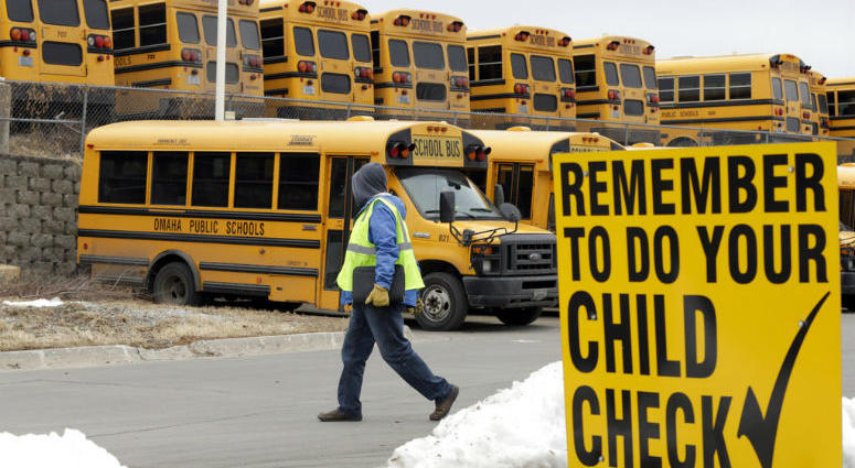 In this Dec. 20, 2018 photo, a driver walks away from the school bus parking lot after his morning shift, in Omaha, Neb.