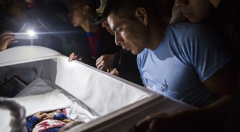 Family members pay their final respects to 7-year-old Jakelin Caal Maquin during a memorial service in her grandparent's home in San Antonio Secortez, Guatemala, Monday, Dec. 24, 2018.