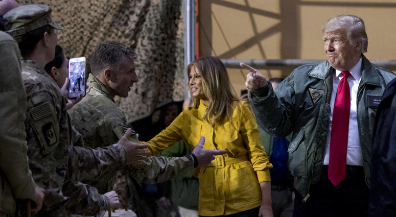 President Donald Trump and first lady Melania Trump greet members of the military as they arrive for a hangar rally at Al Asad Air Base, Iraq, Wednesday, Dec. 26, 2018.