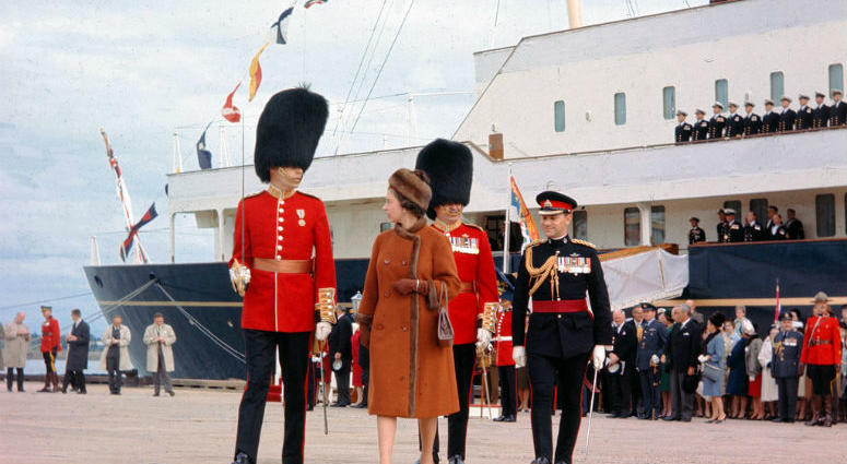 FILE - In this file photo dated Oct. 6, 1964, Britain's Queen Elizabeth II is escorted by Captain G. L. Simpson, as she leaves the Royal Yacht Britannia to inspect the 2nd Battalion of the Canadian Guard, on her arrival at Charlottetown, Canada.