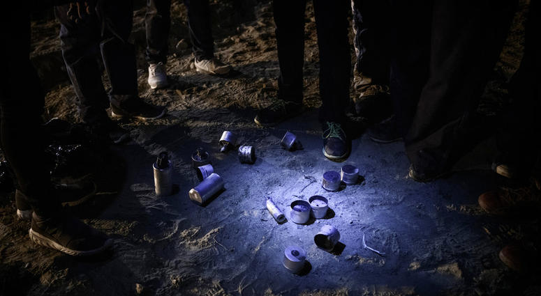Migrants stand by tear gas canisters they collected that were shot towards the Mexican side by U.S. Border Patrol officers after they attempted to get into the U.S. side to San Diego, Calif., from Tijuana, Mexico, Tuesday, Jan. 1, 2019.