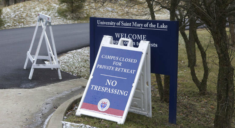 A sign outside the Mundelein Seminary asks the faithful to pray for U.S. based Roman Catholic bishops gathering there for a weeklong prayer retreat, Wednesday, Jan. 2, 2019, in Mundelein, Ill.
