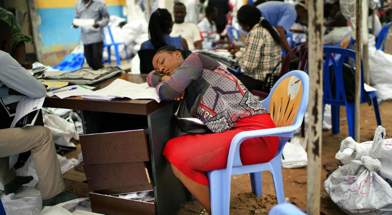 An exhausted Congolese independent electoral commission (CENI) official rests as results are tallied for the presidential election, at a local results compilation center in Kinshasa, Congo, Sunday, Jan. 6, 2019.