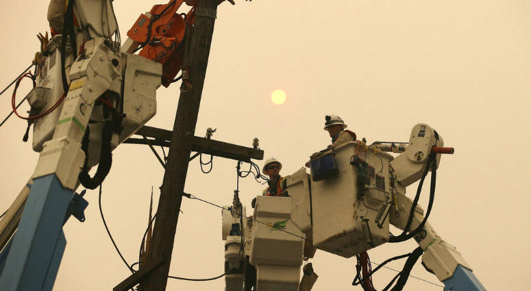 FILE - In this Nov. 9, 2018 file photo, Pacific Gas & Electric crews work to restore power lines in Paradise, Calif.