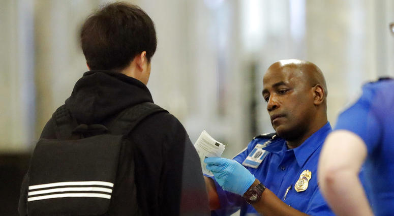 A Transportation Security Administration employee checks an air traveler's identification at Hartsfield Jackson Atlanta International Airport Monday, Jan. 7, 2019, in Atlanta.