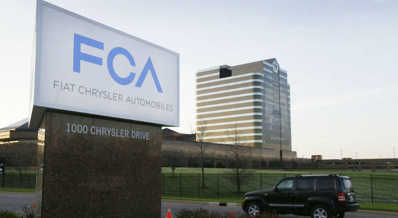 FILE - In this May 6, 2014, file photo, a vehicle moves past a sign outside Fiat Chrysler Automobiles world headquarters in Auburn Hills, Mich.