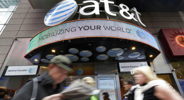 In this Oct. 21, 2014 file photo, people pass an AT&T store in New York's Times Square. AT&T says it will stop selling customer location data to data brokers, as the telecom industry faces backlash that the data has been used improperly.