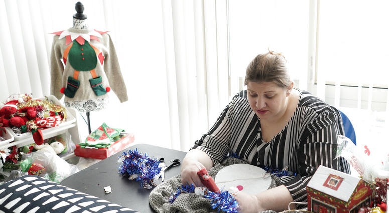 "Doris Cochran works on ""an ugly sweater,"" which she is planning to sell. Cochran is a disabled mother of two young boys living in subsidized housing. She's stockpiling canned foods to ensure her family won't go hungry if her food stamps run out."