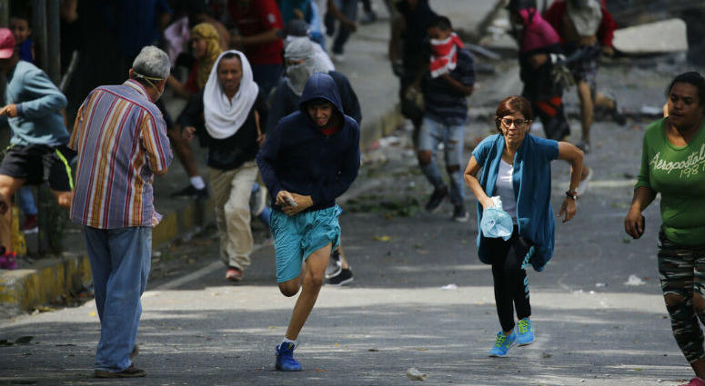 Anti-government protesters run during clashes with security forces as they show support for an apparent mutiny by a national guard unit in the Cotiza neighborhood of Caracas, Venezuela, Monday, Jan. 21, 2019.