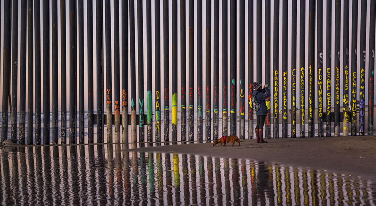 In this Jan. 3, 2019, file photo, a woman takes a photo by the border fence between San Diego, Calif., and Tijuana, as seen from Mexico.