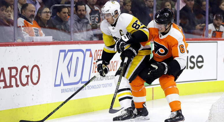 Pittsburgh Penguins' Sidney Crosby (87) and Philadelphia Flyers' Travis Sanheim (6) battle for the puck during the first period of an NHL hockey game, Monday, Feb. 11, 2019, in Philadelphia.