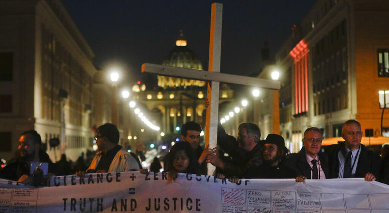 Survivors of sex abuse hold a cross as they gather in front of Via della Conciliazione, the road leading to St. Peter's Square, visible in background, during a twilight vigil prayer of the victims of sex abuse, in Rome, Thursday, Feb. 21, 2019.