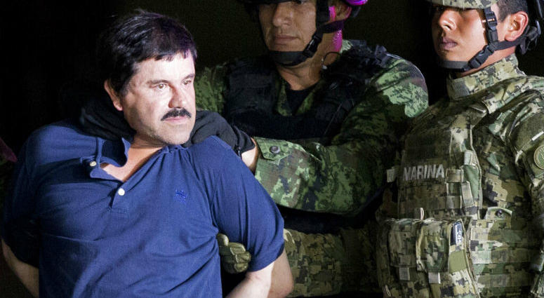 """FILE - In this Jan. 8, 2016 file photo, a handcuffed Joaquin """"El Chapo"""" Guzman is made to face the press as he is escorted to a helicopter by Mexican soldiers and marines at a federal hangar in Mexico City."""