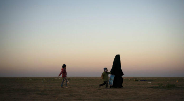A woman walks with her children at a U.S.-backed Syrian Democratic Forces (SDF) screening area after being evacuated out of the last territory held by Islamic State militants, in the desert outside Baghouz, Syria, Friday, March 1, 2019