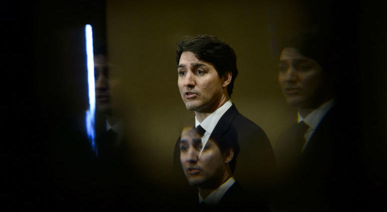 FILE - In this March 8, 2019, file photo, Prime Minister Justin Trudeau is seen through a beveled pane of glass in a door as he takes part in a news conference in Iqaluit, Nunavut, Canada.
