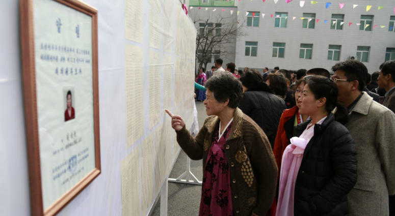 People inspect the list of voters as portrait of a candidate for the national legislature is displayed on the left, during the election at a polling station in Pyongyang, North Korea, Sunday, March 10, 2019.
