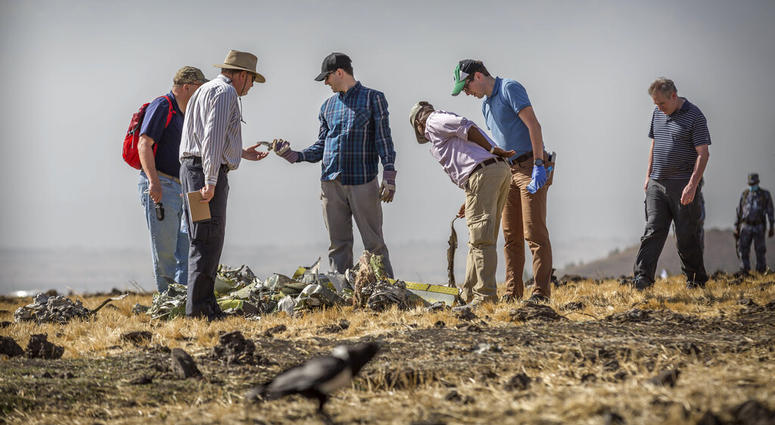 Officials from the Aviation Industry Corporation of China pray March 12, 2019, next to offerings of fruit, breads and incense sticks, at the scene where the Ethiopian Airlines Boeing 737 Max 8 crashed shortly after takeoff.