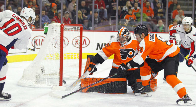 Washington Capitals' Brett Connolly, left, scores past Philadelphia Flyers goalie Carter Hart, center, and Ivan Provorov, right, during the first period of an NHL hockey game Thursday, March 14, 2019, in Philadelphia.