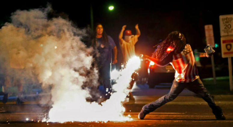 Edward Crawford Jr., returns a tear gas canister fired by police who were trying to disperse protesters in Ferguson, Mo.