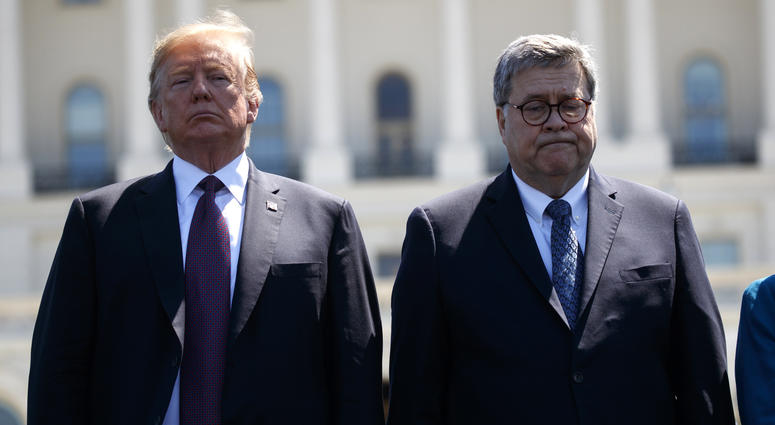 President Donald Trump stands with Attorney General William Barr.