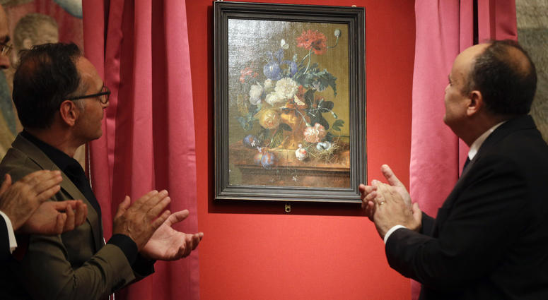 """German Foreign Minister Heiko Mass, left, and Italian Culture Minister Alberto Bonisoli watch the unveiling of the """"Vase of Flowers"""" painting by Jan van Huysum, at the Pitti Palace, part of the Uffizi Galleries, in Florence, Italy, Friday, July 19, 2019."""