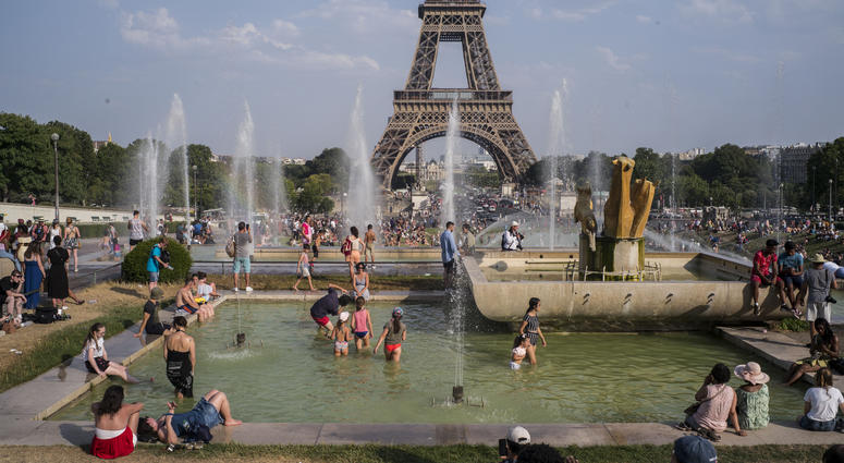 People enjoy the sun and the fountains of the Trocadero gardens in Paris, Thursday July 25, 2019, when a new all-time high temperature of 42.6 degrees Celsius (108.7 F) hit the French capital.