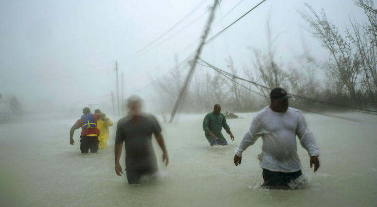 Volunteers walk under the wind and rain from Hurricane Dorian through a flooded road.