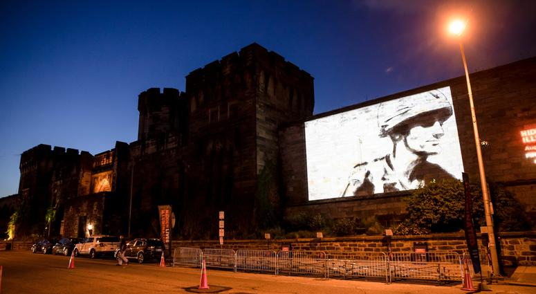 """A guest film by Dee Hibbert-Jones and Nomi Talisman, titled """"Last Day of Freedom"""" is projected on the wall of Eastern State Penitentiary in Philadelphia."""