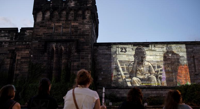 """People view incarcerated filmmaker Robert's animated short titled """"A Special Person"""" projected on the wall of Eastern State Penitentiary in Philadelphia."""
