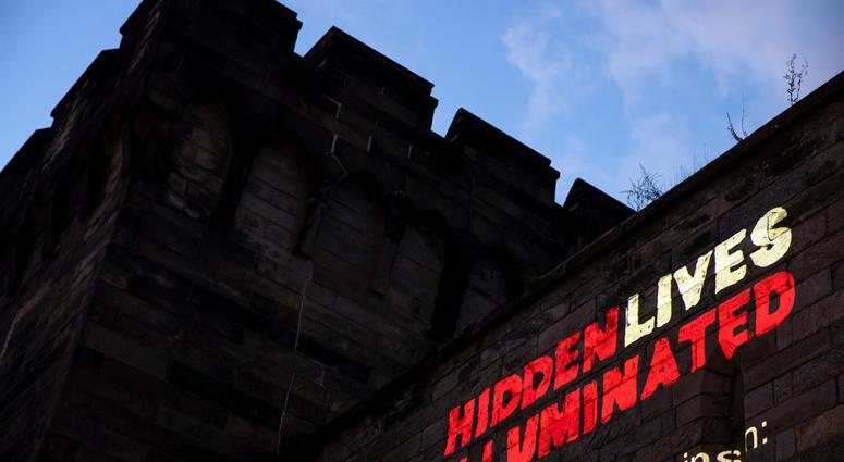 """A new exhibit titled """"Hidden Lives Illuminated"""" is projected on a wall of the Eastern State Penitentiary, a former prison that's now a museum."""