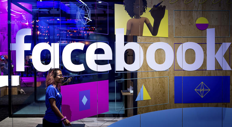 April 18, 2017: A conference worker passes a demo booth at Facebook's annual F8 developer conference, in San Jose, Calif.