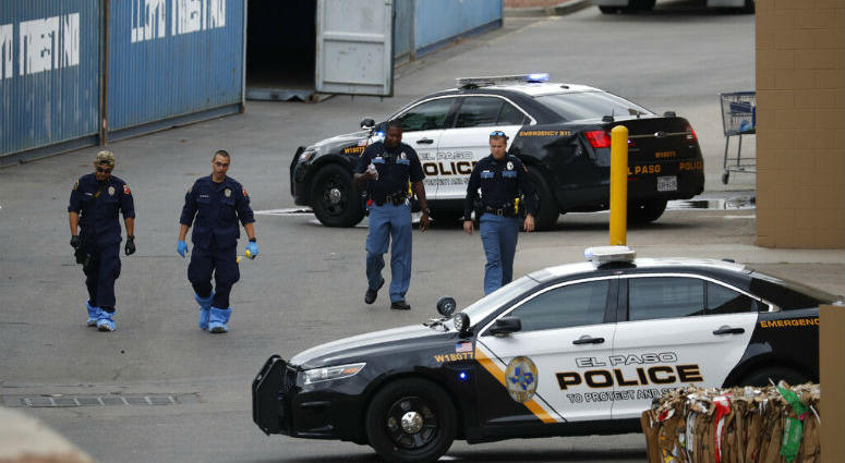 Police officers walk behind a Walmart at the scene of a mass shooting at a shopping complex in El Paso, Texas.