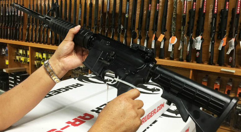 a customer looking at an AR-15 semi-automatic rifle
