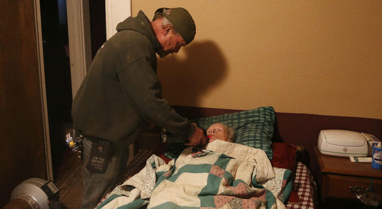 Brad Weldon gives his 89-year-old mother Norma Weldon a drink at their home in Paradise, Calif.