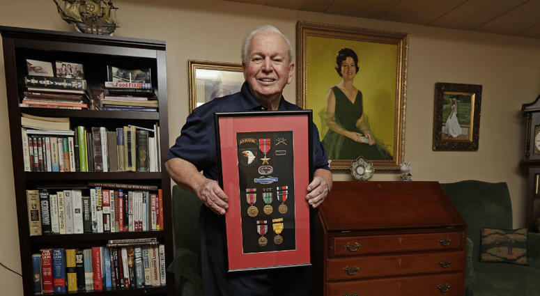 In this Wednesday, May 22, 2019, photo, D-Day veteran Eugene Deibler poses for a photo with his medals from WWII at his home in Charlotte, N.C.