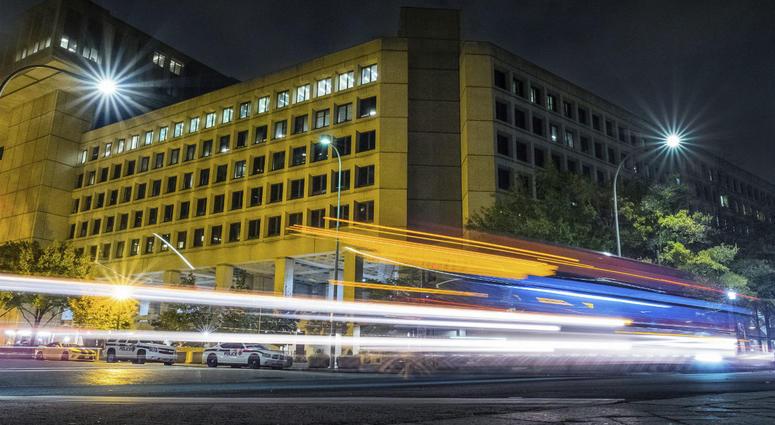 In this Nov. 1, 2017, file photo, traffic along Pennsylvania Avenue in Washington streaks past the Federal Bureau of Investigation headquarters building.