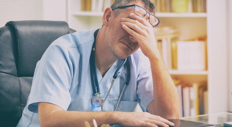 Overworked doctor in his office - stock photo