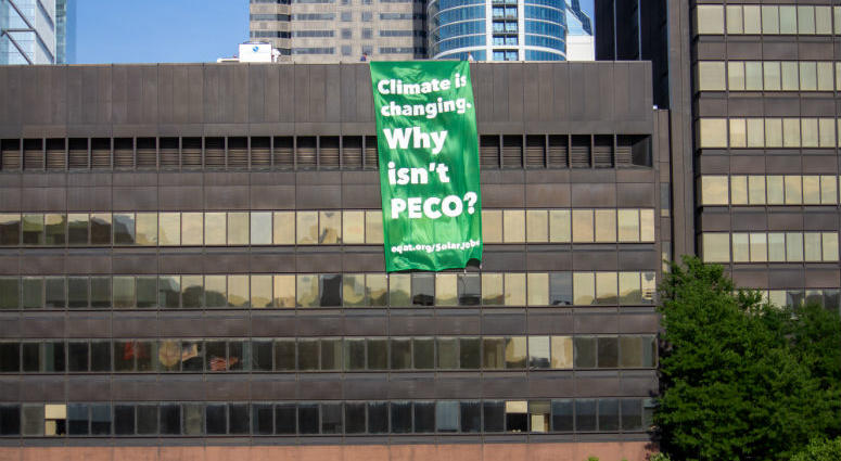 "On a broiling mid-July afternoon, three activists from EQAT (pronounced ""equate"") were arrested for unfurling a banner from the roof of PECO's headquarters on Market Street declaring, ""Climate is changing — Why isn't PECO?"""