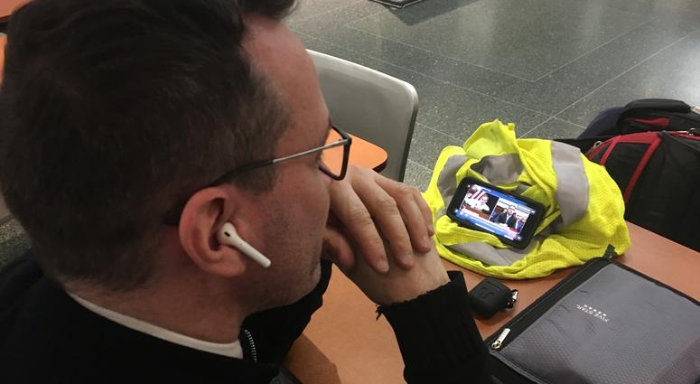 A man watches Michael Cohen testify before the House Oversight Committee on his iPhone while grabbing breakfast at the Comcast Center, Feb. 27, 2019.