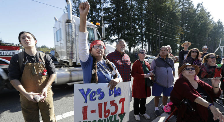 A supporter of Initiative 1631 holds a sign referencing the Nisqually Indian Tribe during a rally supporting the November ballot measure in Washington state that would charge a fee on carbon emissions from fossil fuels.