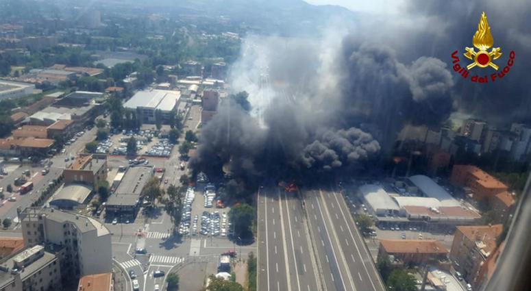 In this photo released by the Italian firefighters, an helicopter view of the explosion on a highway in the outskirts of Bologna, Italy, Monday, Aug. 6, 2018.