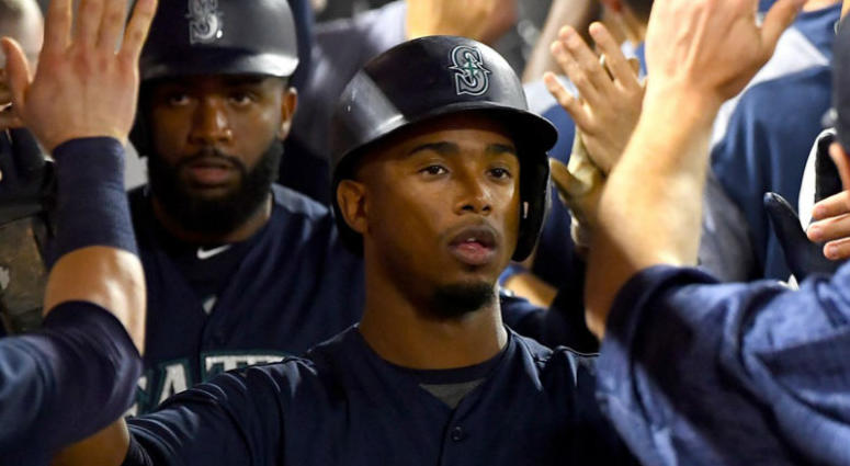 Seattle Mariners left fielder Denard Span (4) and shortstop Jean Segura (2)are greeted in the dugout