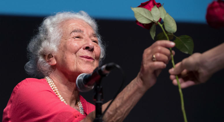 """In this Sept. 15, 2016 file photo British writer Judith Kerr holds a rose in Berlin, Germany. Judith Kerr, author and illustrator of the bestselling """"The Tiger Who Came to Tea"""" and other beloved children's books, has died at the age of 95."""