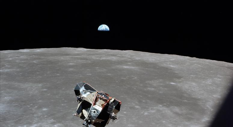 Astronaut Mike Collins captures Earth, the moon, the Eagle, and the edge of the Command Module's window in a single shot.
