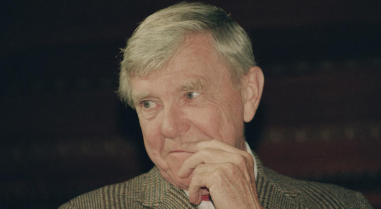 """In this Tuesday, Feb. 23, 1993 file photo, writer Russell Baker, ponders a reporter's question during a New York news conference where he was presented as the successor to host Alistair Cooke for the PBS series """"Masterpiece Theatre."""""""