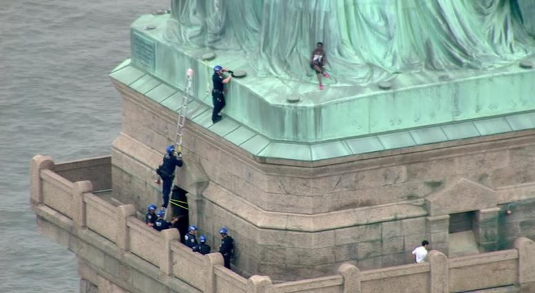 Woman climbs on Statue of Liberty